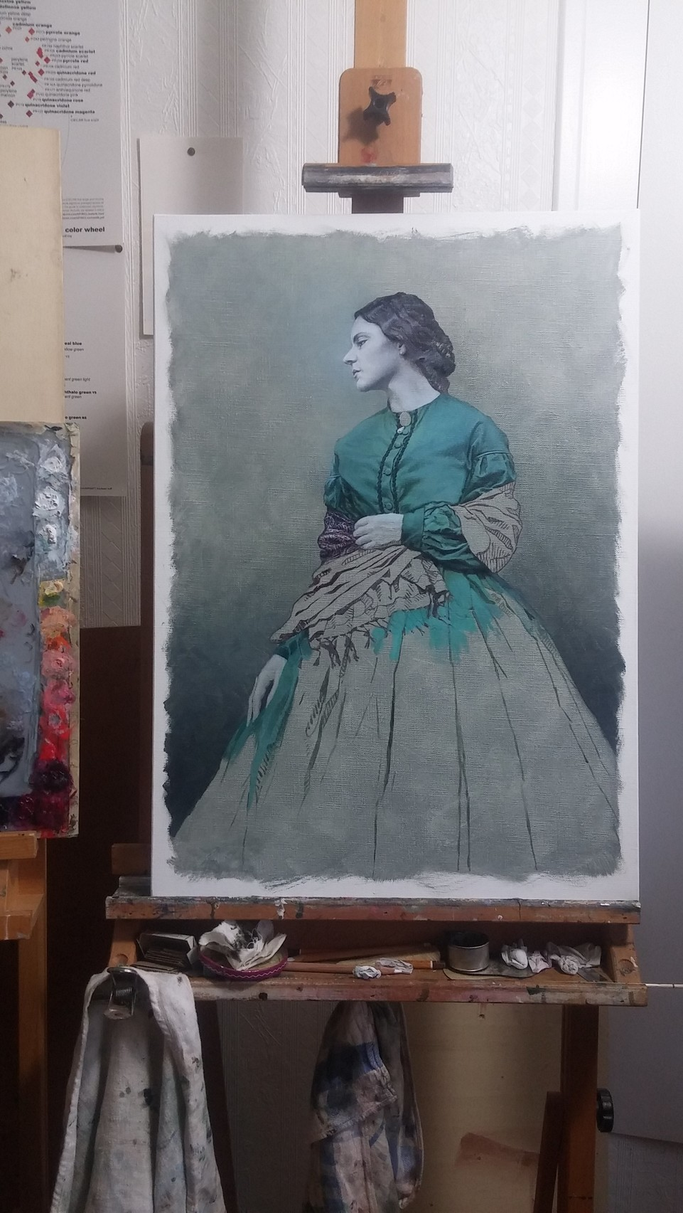 an oil painting portrait under way, sitting on an easel, next to a palette
